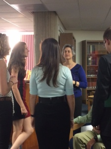Seniors huddle with Professor Castaldo right before beginning their presentations.